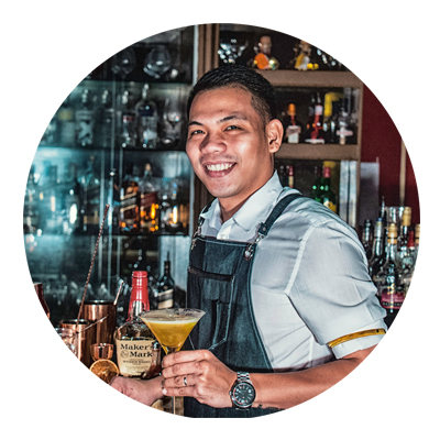 smiling bartender with cocktail in his hand