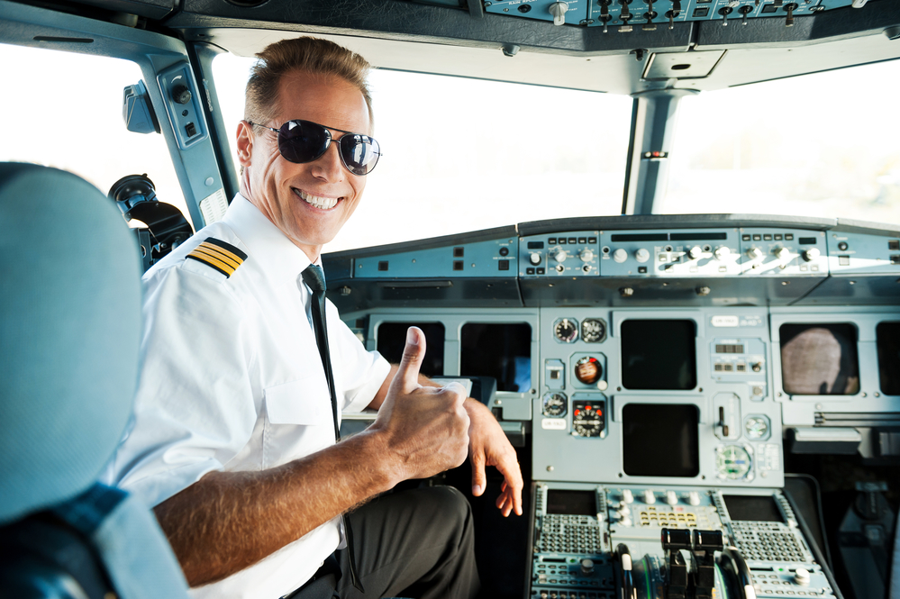 Commercial Pilot smiling in the cockpit with thumb up
