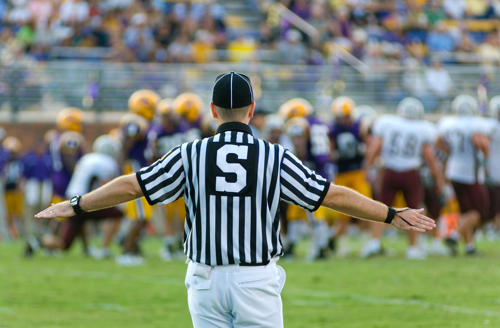 American Football Sports Referee at work on the field
