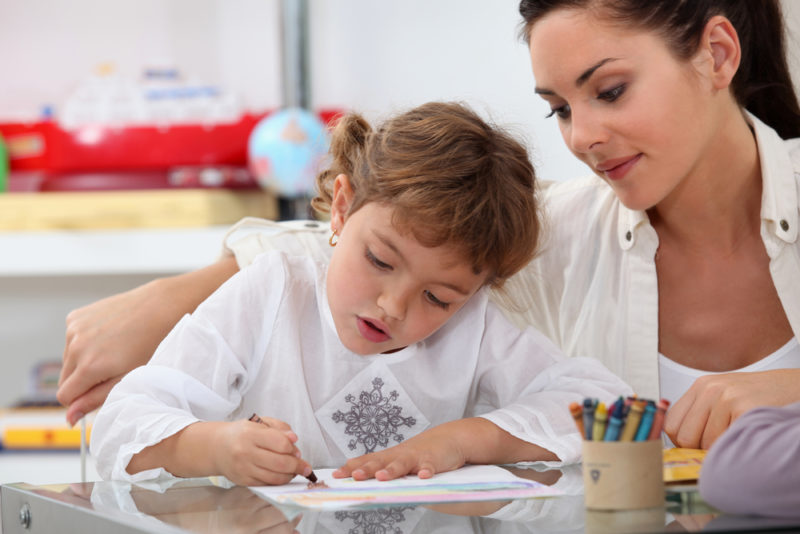 Au pair watching her pupil draw