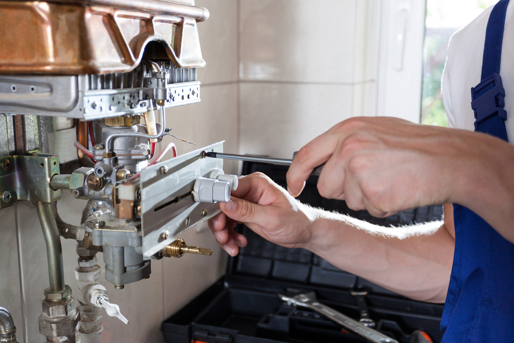 boilermaker fixing a gas water heater with a screwdriver