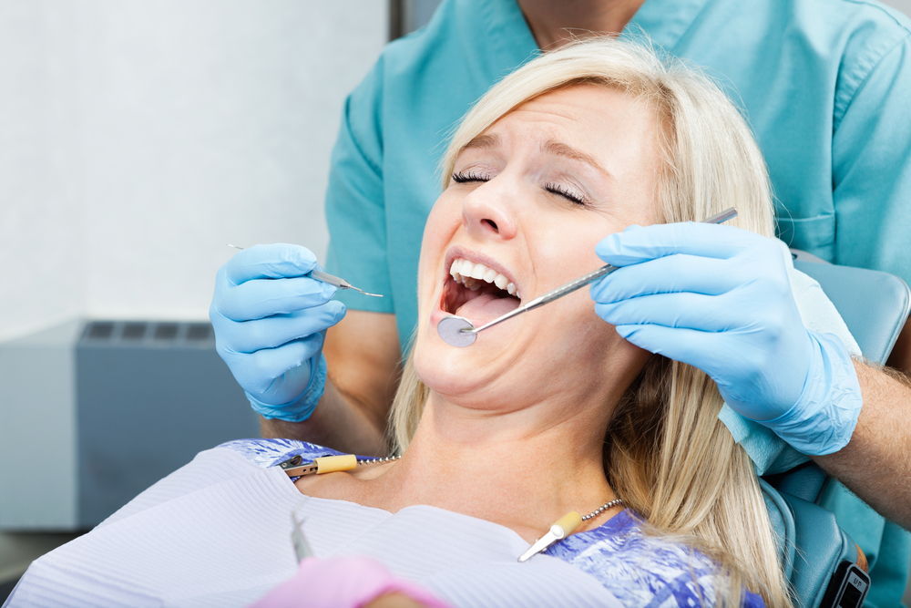 Mouth hygienist helps a young female patient at clinic