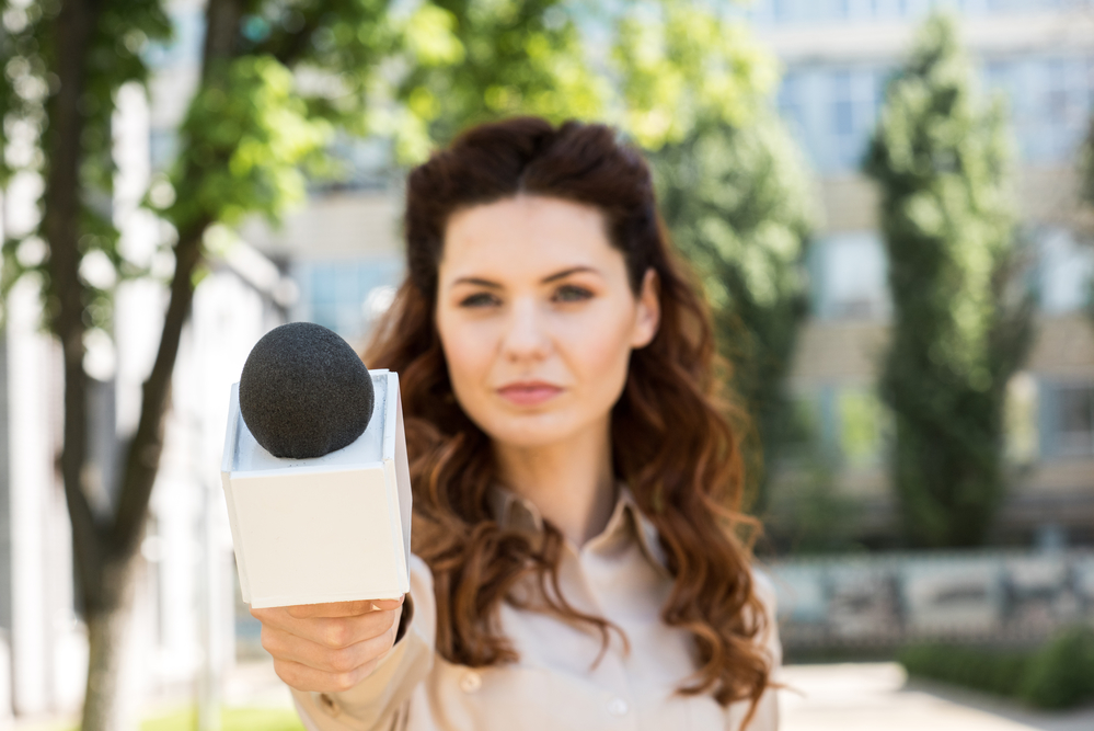 Female yournalist aiming the microphone towards the point of view